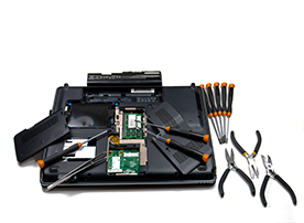 A view of the underside of an open computer surrounded by precision tools isolated on white